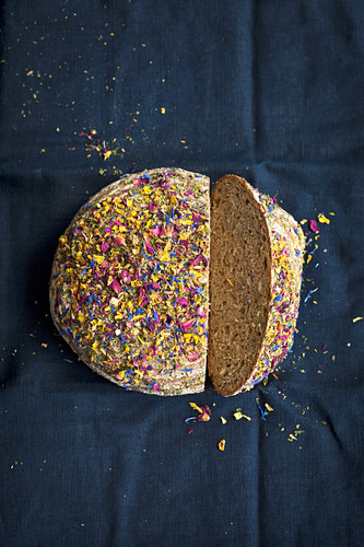 A loaf of wholemeal bread topped with edible flowers, sliced
