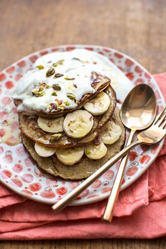 Bananen-Pancakes aus glutenfreien Haferflocken mit Pistazien, Naturjoghurt und Sirup
