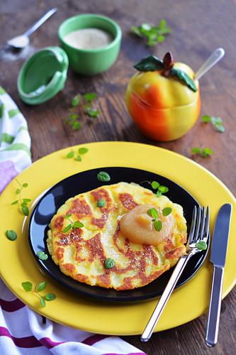A large potato pancake with applesauce, sugar and fresh mint