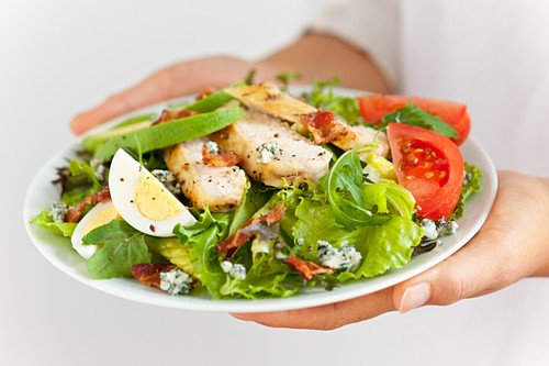 Serving salad with chicken and eggs