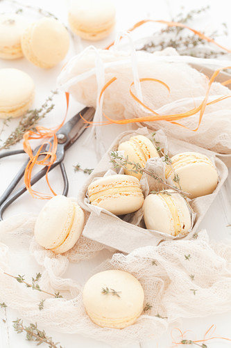 Orange macarons with thyme in a gift box