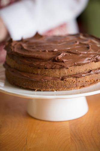 A cake being made: chocolate cream being spread onto a cake
