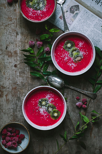 Raspberries smoothies in three bowls on a wooden table with a newspaper