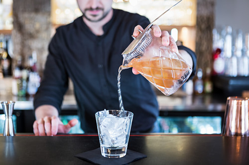 A bartender pouring a cocktail