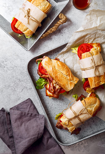 Fresh baguette sandwich bahn-mi styled, bacon, roasted cheese, tomatoes and lettuce on metallic tray background