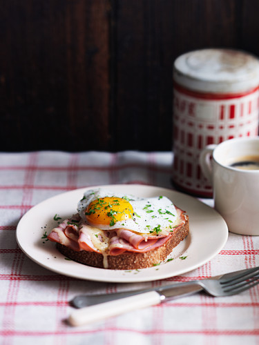Croque Madame toast with ham and fried egg, and a cup of coffee