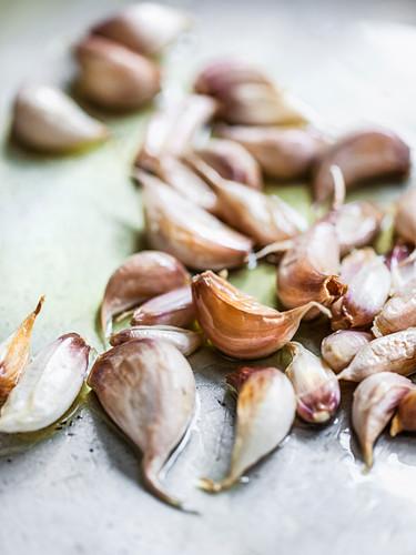 Ungeschälte Knoblauchzehen auf Olivenöl