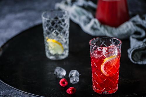 Raspberry iced tea with ice cubes and lemon zest