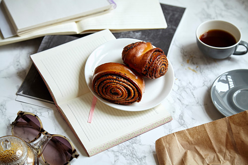 Overhead shot of sweet rolls with poppy seeds on marble table piled up with study materials