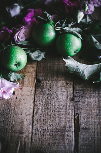 Green apples with leaves and pink flowers