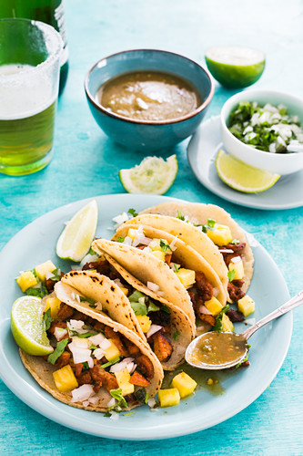 Tacos al pastor (with pineapple and green sauce, onions, cilantro and lime)