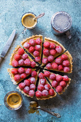 Freshly baked custard tart decorated with fresh raspberries on a table