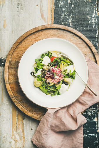 Flat-lay of fresh green summer salad with artichokes, olives, soft cheese and red onion in white plate over rustic wooden background