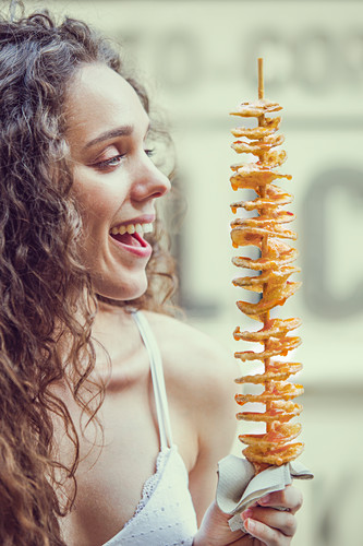 Junge Frau isst Twisted Potatoes auf Streetfood-Markt