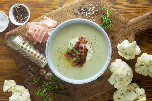 Cauliflower soup with ingredients on a wooden surface