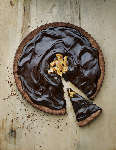 A chestnut torte with a piece cut on a wood background