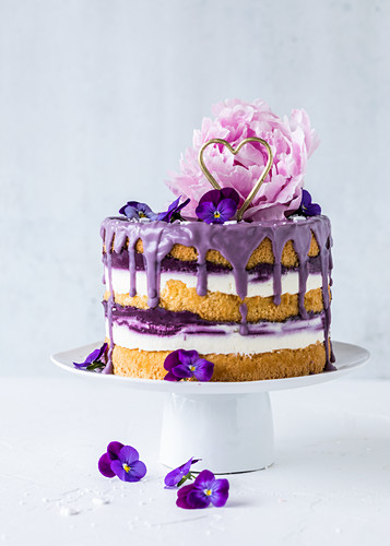 A blueberry drip cake decorated with a peony