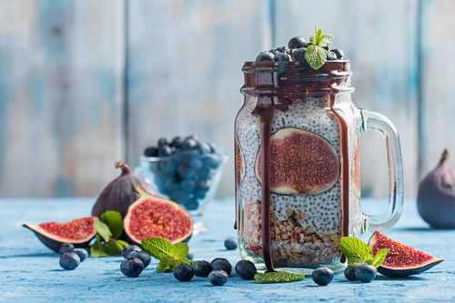 Glass jar of healthy breakfast with muesli, pudding with chia seeds, fresh fig and berries