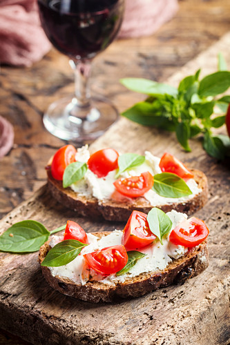 Crostini appetizers with cherry tomatoes, basil, and cheese