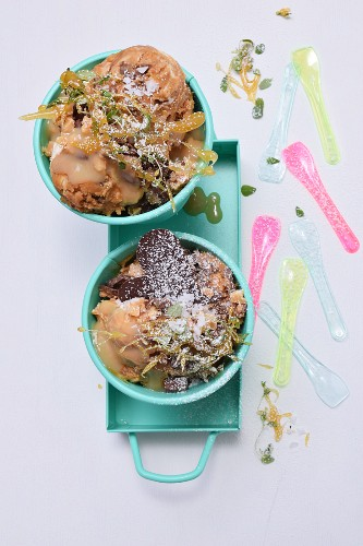 Caramel ice cream with thyme caramel, caramel sauce and chocolate in turquoise pots with ice cream spoons