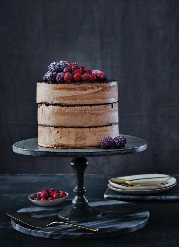 Geschichtete Schokoladentorte mit Schokosahne, geeisten Brombeeren und Cranberries