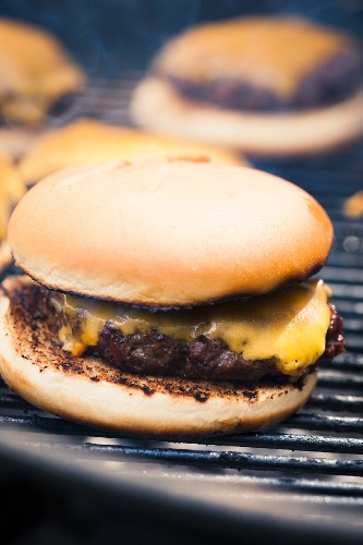 Cheeseburger in a bun on the grill