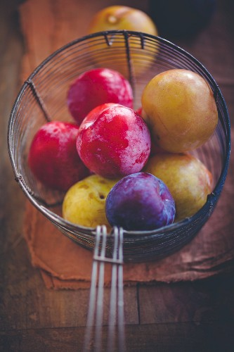 Various plums in a wire basket