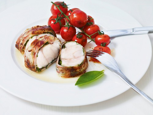 Fish wrapped in bacon served with vine tomatoes