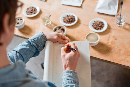 A coffee taster making notes