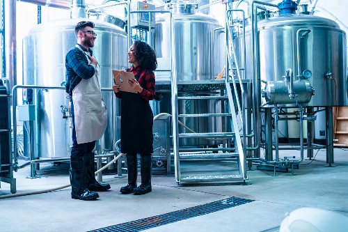 A beer brewer and a colleague taking in front of beer tanks (USA)