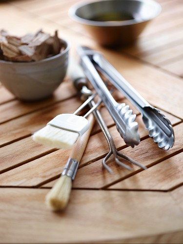 Various grilling utensils on a wooden board