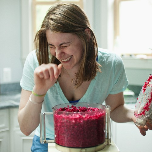 A woman reacting to the smell of horseradish in a blender