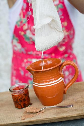 Freshly made almond milk next to goji berries and carob powder
