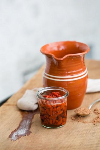 Almond milk in a terracotta jug, goji berries and carob powder
