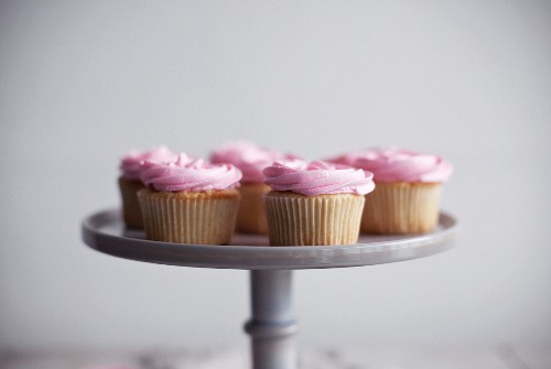 Cupcakes with pink cream frosting on a cake stand