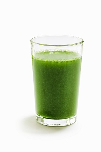 A green wheatgrass smoothie on a white surface