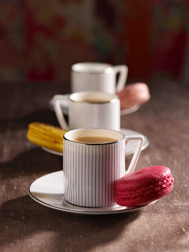 Tea in striped cups with macaroons