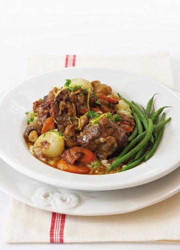Oxtail stew with onions, carrots and mushrooms
