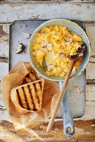 Scrambled egg with truffles in a pan with toast