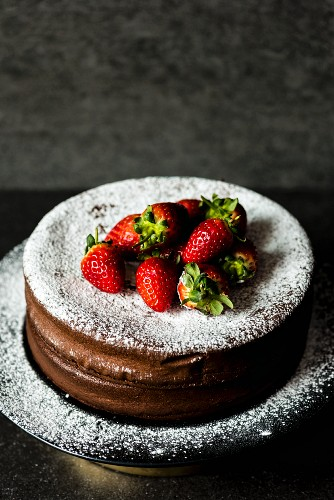 Chocolate cake with icing sugar and strawberries