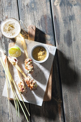 Minced meat and lemongrass skewers with a yellow pepper dip (seen from above)