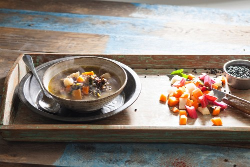 Steaming lentil soup on a wooden tray