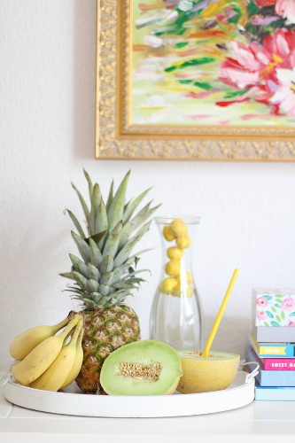 A carafe of water, bananas, pineapple and half a melon on a tray