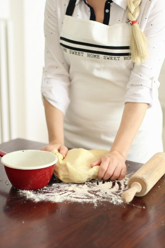 Woman Kneading Dough on Floured Counter in Kitchen