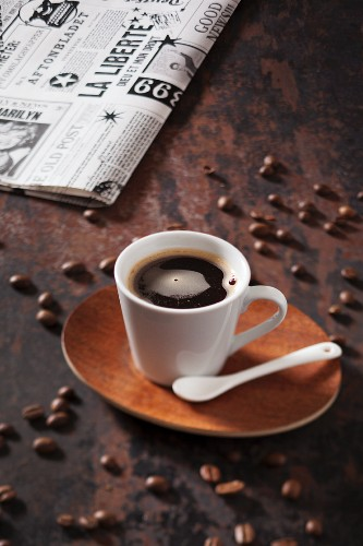 A cup of coffee with a daily newspaper in the background