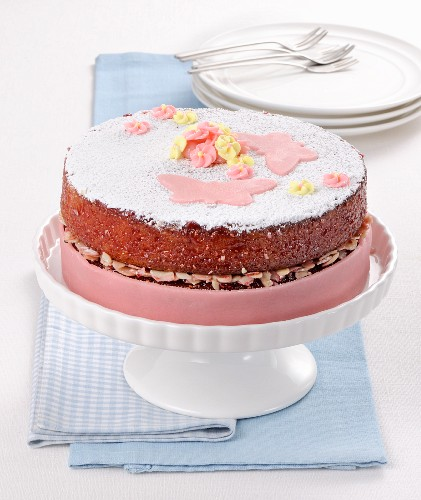A celebratory almond cake decorated with pink marzipan