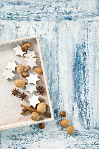 Cinnamon stars, cinnamon sticks, star anise and nuts in a wooden crate (seen from above)