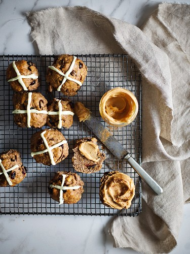 Hot cross buns on a wire rack with macadamia nut butter