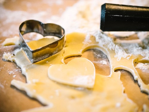 Heart-shaped biscuits being cut out of shortcrust pastry (close-up)