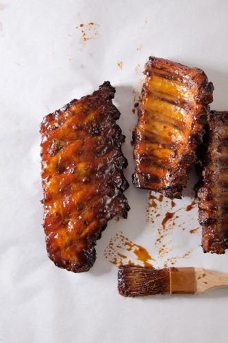 Barbecued pork ribs on a white surface (seen from above)